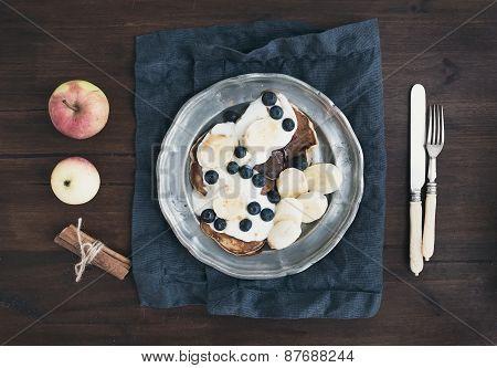Breakfast Set On Dark Wooden Desk: Apple And Cinnamon Pancakes With Yogurt, Banana, Blueberry And Ma