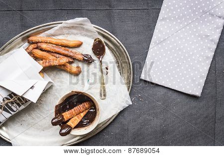 Churros With Chocolate Sauce On A Metal Plate