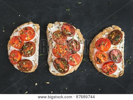 Ricotta And Cherry-tomato Sandwiches With Fresh Thyme Over A Dark Stone Surface