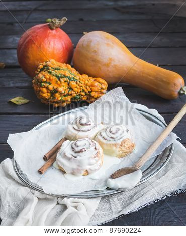 Cinnamon Pumpkin Buns With Creamy Cheese Icing And Ripe Pumpkins Over A Dark Wood