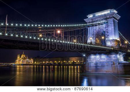 The Night View Of The Parlament Building And The Danube Under The Chain Bridge In Budapest