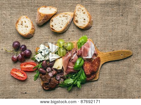 Cheese And Meat Platter With Fresh Grapes, Cherry-tomatoes, Olives, Herbs And Bread Pieces On A Rust