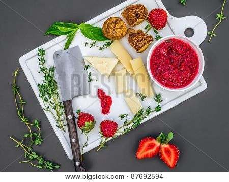 A Set Of Cheese, Fresh Strawberries, Herbs, Dried Figs And Raspberry Jam Woth A Cheese Knife On A Wh