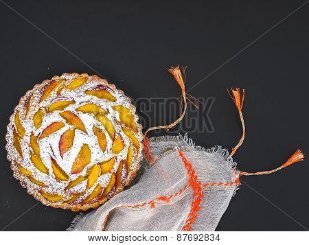 Peach Pie With Sugar Powder Over A Linen Table Cloth On Dark