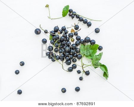 Black-currant Berries And Green Leaves Over A White Wooden Sufrace
