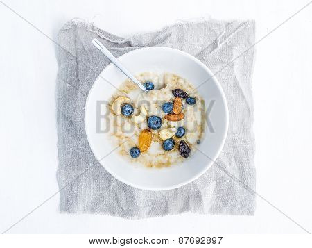 Oat Porridge With Fresh Blueberry, Nuts And Honey In A White Ceramic Bawl On White