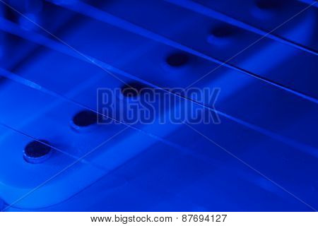 Guitar pickup and strings in blue light