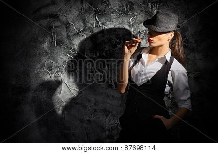 Young woman with cigar on grey wall