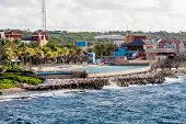 stock photo of curacao  - Swimming pool between colorful resort on Curacao and surf hitting rocks - JPG