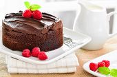 stock photo of chocolate fudge  - Fresh Home Made Sticky Chocolate Fudge Cake With Raspberries and a jug of pouring cream - JPG