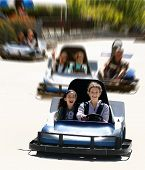 foto of amusement park rides  - girls on go cart with a motion blur background - JPG