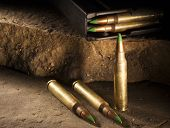 stock photo of cartridge  - Green tipped cartridges and loaded magazine on rocks - JPG