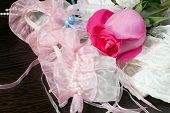 stock photo of garter  - Beautiful pink rose garter and white stockings lying on a table - JPG