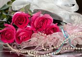 stock photo of garter  - Beautiful pink roses pearl beads and garter lying on a table - JPG