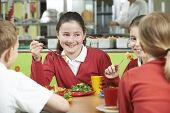 stock photo of school lunch  - Group Of Pupils Sitting At Table In School Cafeteria Eating Lunch - JPG