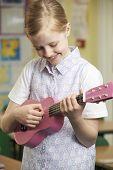 pic of ukulele  - Girl Learning To Play Ukulele In School Music Lesson - JPG