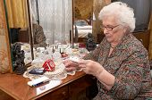 stock photo of prescription  - Senior caucasian woman about ninety years old sits near the mirror takes out pills and reads prescriptions in her bed room  - JPG