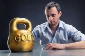 picture of kettlebell  - Businessman looks at a gold kettlebell - JPG