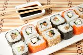 pic of soy sauce  - sushi assortment on white plate with soy sauce over bamboo background - JPG