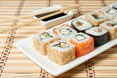 foto of soy sauce  - sushi assortment on white plate with soy sauce over bamboo background - JPG