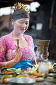 picture of ceremonial clothing  - Young Balinese woman praying in traditional ceremonial clothing - JPG