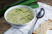 stock photo of leek  - leek cream soup in a white bowl with spoon napkin and fresh leek od rustic wood - JPG