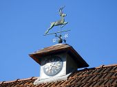 image of wind-vane  - Stag weather vane atop a clock tower set against a blue sky - JPG