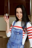 pic of overalls  - Brunette housewife wearing in blue denim overalls holding a glass of juice and a glass of red smiling - JPG