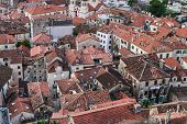 stock photo of red roof tile  - The view over red tiles roofs of the old center of Kotor Montenegro from the ancient fortress wall upside the mountain - JPG