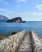 picture of sea-scape  - The view over Saint Nikolas island and the Adriatic sea from the top of the ancient citadel in the old town center of Budva the path seems to lead directly into the sea - JPG
