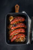 stock photo of onion  - Sausages baked with onion rings in brytfance - JPG