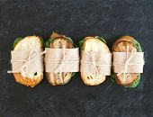 picture of paper craft  - Chicken and spinach sandwiches wrapped in craft paper over a dark stone background with a copy space - JPG