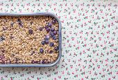 stock photo of oats  - Oat granola with fresh berries in a silver baking dish over a flower patterned background - JPG