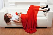 pic of yoke  - Girl lying on the sofa her red dress and a flower in her hand - JPG