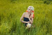 stock photo of tall grass  - A girl sits among the tall grass in the meadow. ** Note: Soft Focus at 100%, best at smaller sizes - JPG