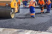 stock photo of vibrator  - Roller and workers on asphalting and repair of city streets - JPG