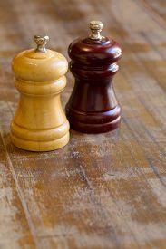 stock photo of salt shaker  - Wooden salt and pepper shakers on wooden table - JPG