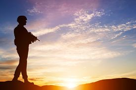 image of army soldier  - Armed soldier with rifle standing and looking on horizon - JPG