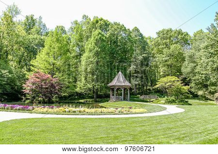 Gazebo And Bridge In Green Public Garden