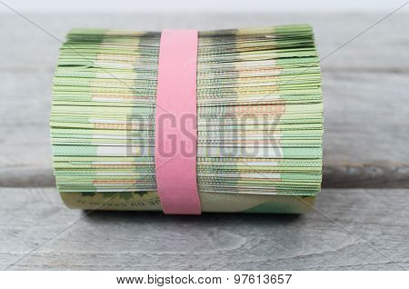 Roll Of Money On Wooden Table