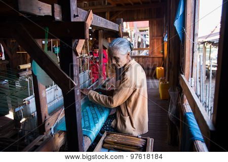 INLE LAKE, MYANMAR, FEB 27, 2015: An unidentified Burmese woman weaving clothe from lotus silk in Inle Lake, Myanmar. Silk was produced from lotus is a speciality of Inle Lake area.