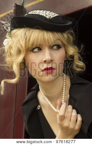 Elegant retro / fifties style woman playing with her pearl necklace