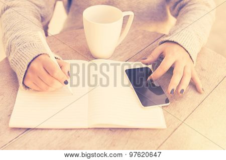 Girl Writes In A Notebook, With Cell Phone And Cup Of Coffee, Vintage Color Effect