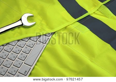 Keyboard In The Yellow Reflective Safety Vest And Wrench