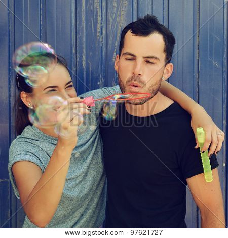 Beautiful happy smiling woman embracing your boyfriend blowing soap bubbles. Portrait of young attractive heterosexual couple outdoor over grunge blue background, image toned and noise added.