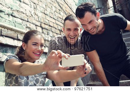 Friends taking self photo with smart phone. Selfie, friendship, young adult, leisure concept.