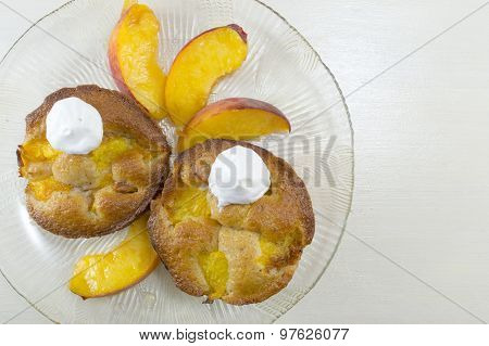 Homemade Fruit Muffins Decorated With Cream And Fresh Peach Slices