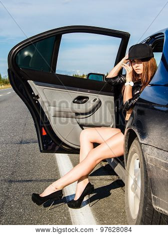 Beautiful Young Woman Sitting At The Back Seat Of A Car