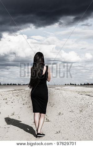 Woman In A Black Clothes In A Desert