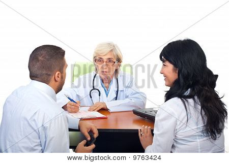 Doctor Having Conversation With Young Couple
